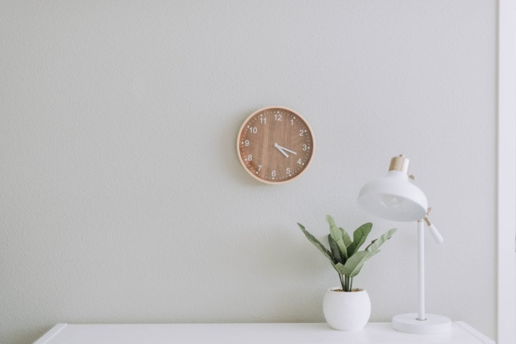 Picture of clock above white desk with plant and lamp